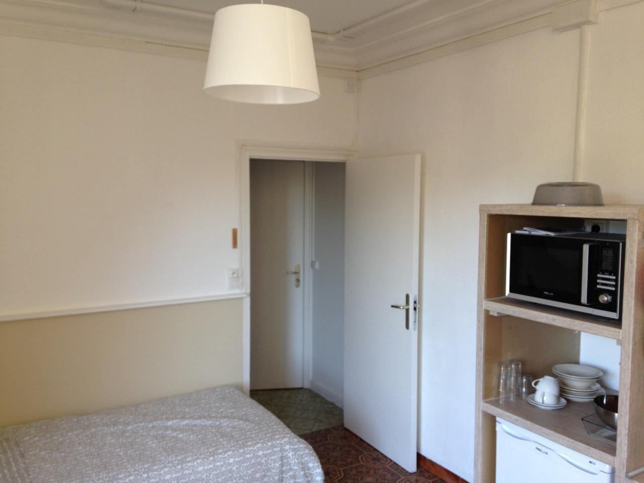 Aperçu lit et espace cuisine, accès dressing et porte d'entrée
